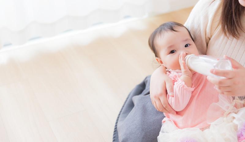 ママに抱かれて哺乳瓶でミルクを飲む赤ちゃん
